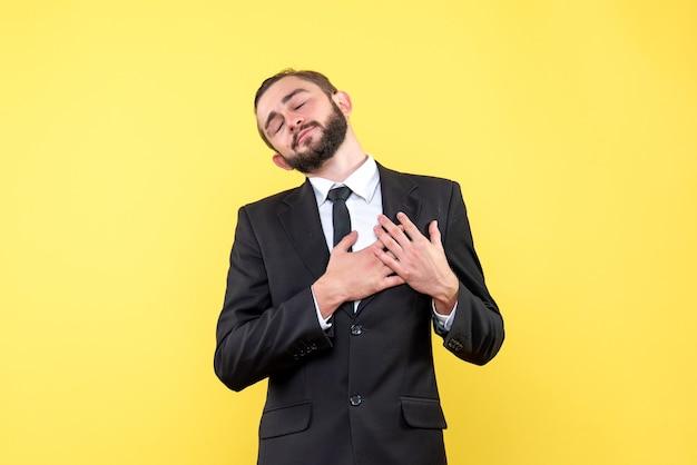 Bebaarde romantische kerel die zijn handen op zijn hart houdt