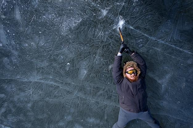 Bebaarde roodharige alpinist in beschermende gele glazen met ijsbijl clibing omhoog op ijzige rots, in een poging niet naar beneden te vallen