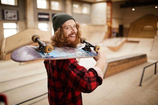 Bebaarde schaatser die bij camera glimlacht