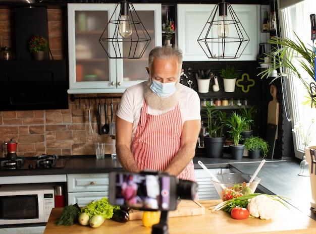 Bebaarde senior blogger video opnemen op camera in keuken.