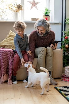 Bebaarde senior man en zijn schattige kleine kleinzoon spelen met hond zittend in fauteuil door versierde spar tegen raam op kerstavond