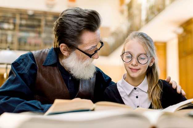 Bebaarde senior man grootvader en kleine schattige kleindochter leesboek samen, zittend aan tafel in oude vintage bibliotheek