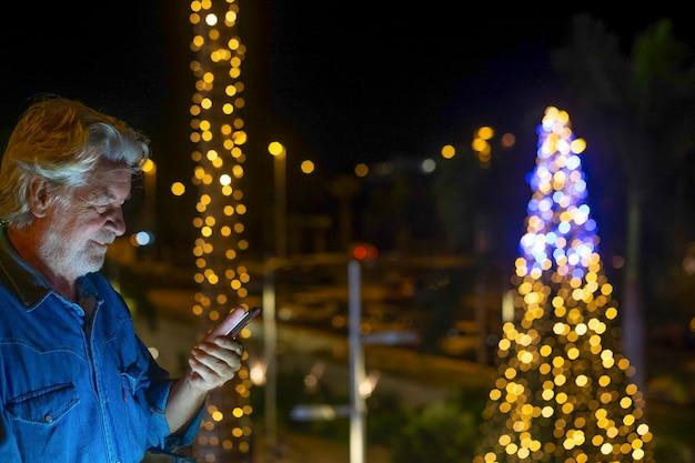 Bebaarde senior man met wit haar met behulp van slimme telefoon buiten in de nacht met verlichte kerstboom achter hem. concept van ouderen tech en sociaal