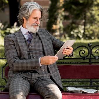 Bebaarde senior mannelijke browsen tablet