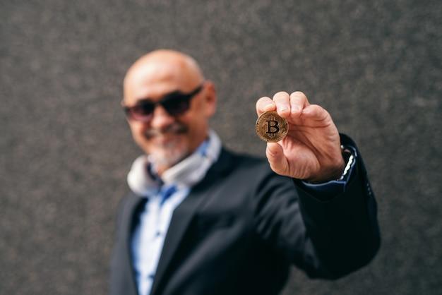 Bebaarde senior volwassen rijke zakenman met bit-munt.
