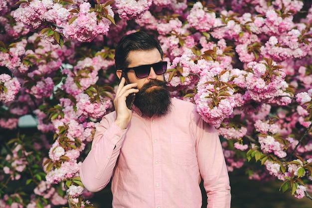 Bebaarde serieuze man praten via de mobiele telefoon. modieuze man in trendy bril. lente bloemen. lente roze sakura bloesem.