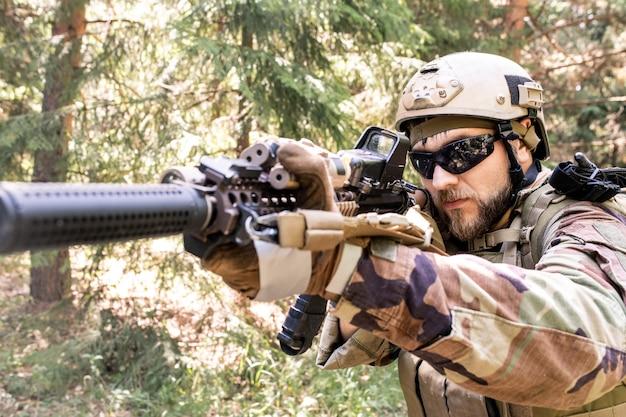 Bebaarde sluipschutter in zonnebril en helm gericht op doelwit kijkend door richtkijker in bos