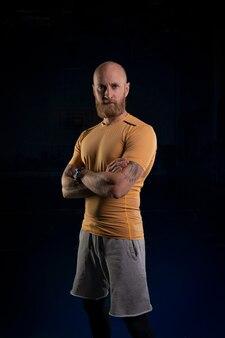 Bebaarde sportman met tatoeages op zijn onderarmen staat met zijn armen over elkaar