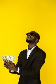 Bebaarde stijlvolle jonge afro-amerikaanse man houdt dollars in beide handen en gaat ze overgeven, in zonnebril en zwart pak