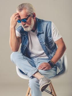 Bebaarde stijlvolle volwassen man in spijkerbroek dragen en zonnebril.