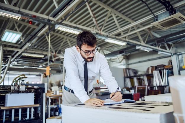 Bebaarde supervisor met bril die de kwaliteit van gedrukte vellen controleert en notities in notitieboekje opschrijft