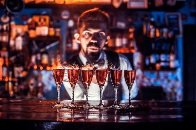 Bebaarde tapster verse alcoholische drank gieten in de glazen op de balk