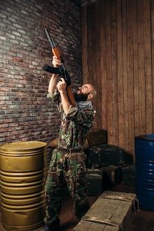 Bebaarde terrorist die het kalashnikov-geweer omhoog houdt. terrorisme en terreur, soldaat in kaki camouflage