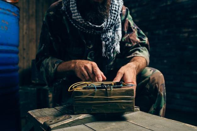 Bebaarde terrorist in uniform die een bom kookt, mannelijke mojahed met explosief. terrorisme en terreur, soldaat in kaki camouflage