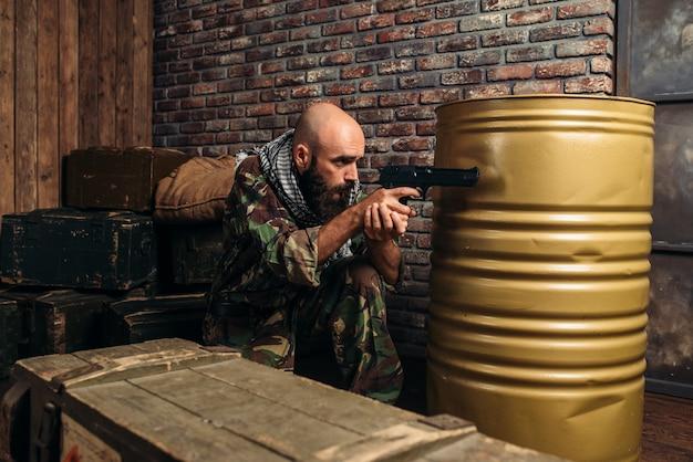 Bebaarde terrorist in uniform gericht met een pistool, mannelijke mojahed met wapen, wahab. terrorisme en terreur, soldaat in kaki camouflage