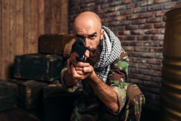 Bebaarde terrorist in uniform gericht vanuit een pistool, mannelijke mojahed met wapen, wahab. terrorisme en terreur, soldaat in kaki camouflage Premium Foto