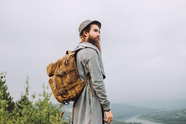 Bebaarde toeristenman in een grijze hoed met een rugzak staat en kijkt naar het landschap