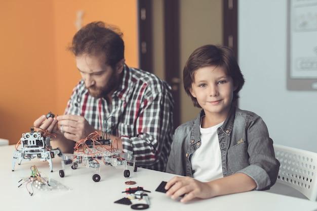 Bebaarde vader en zoon bouwen thuis robot.