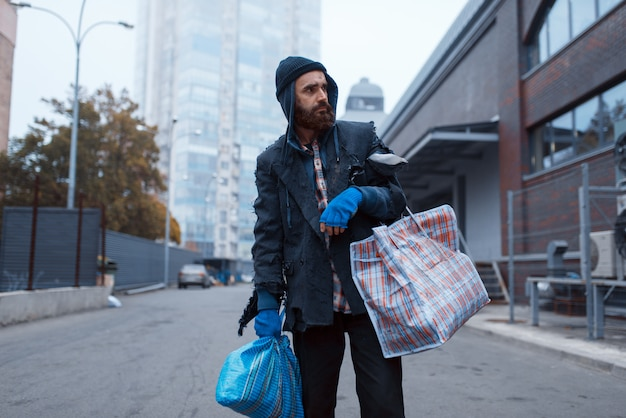 Bebaarde vagebond man met tas op straat in de stad.