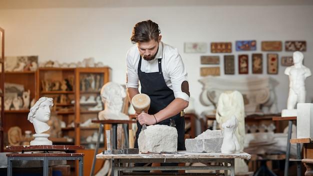 Bebaarde vakman werkt in witte steenhouwen met een beitel. creatieve workshop met kunstwerken.