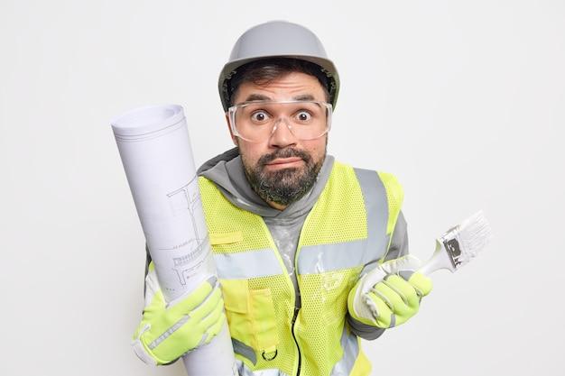 Bebaarde verwarde verraste mannelijke architect weet niet waar hij moet beginnen met schilderen, penseel en papieren blauwdruk draagt beschermende helm, transparante bril en uniform. fabrieksarbeider