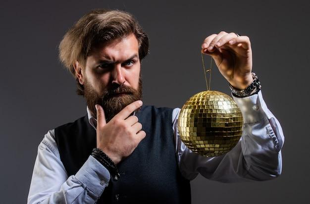 Bebaarde volwassen man houdt gouden discobal, feestuitnodiging concept.