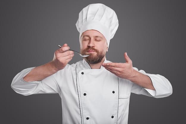 Bebaarde volwassen man in chef-kok uniforme ogen sluiten en ruikende schotel op lepel tijdens het werk in restaurant tegen grijze achtergrond