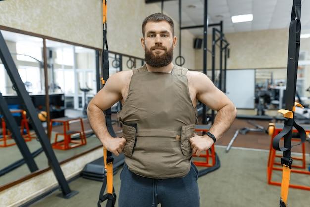Bebaarde volwassen man in de sportschool, gekleed in kogelvrij gepantserd vest, militaire sport