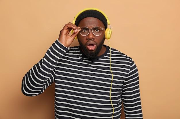 Bebaarde volwassen man kijkt scrupuleus door een ronde bril, heeft een geschokte reactie