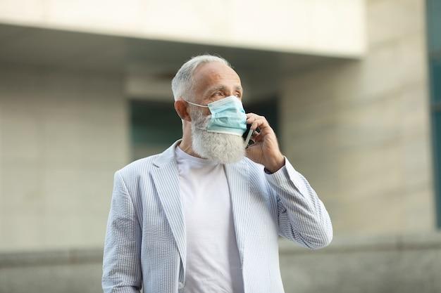 Bebaarde volwassen man met medische masker met behulp van mobiele telefoon buiten