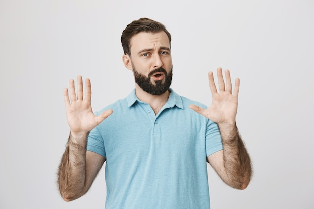Bebaarde volwassen man probeert persoon te kalmeren, handen opheffen