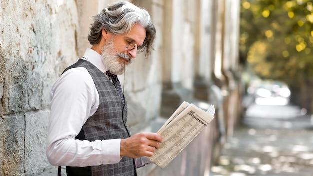 Bebaarde volwassen mannelijke krant lezen