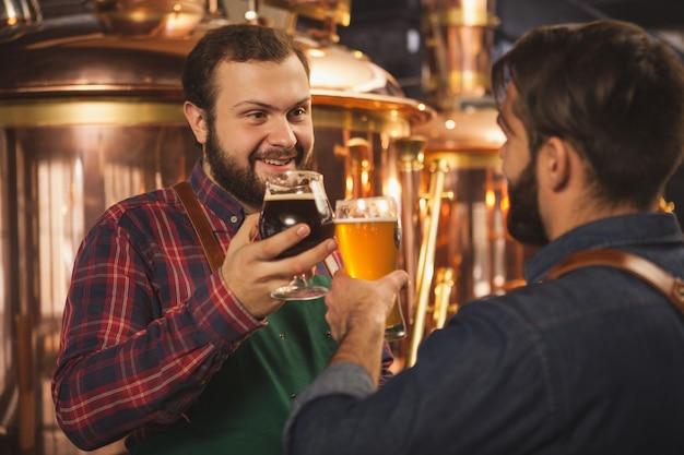 Bebaarde vrolijke brouwer praten met zijn assistent, werken in de productie-fabriek voor bierproductie