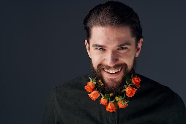 Bebaarde vrolijke man bloemen verschillende romantiek decoratie zwarte ruimte