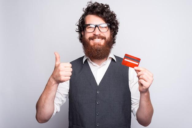 Bebaarde vrolijke man met een creditcard en een duim die naar de camera glimlacht