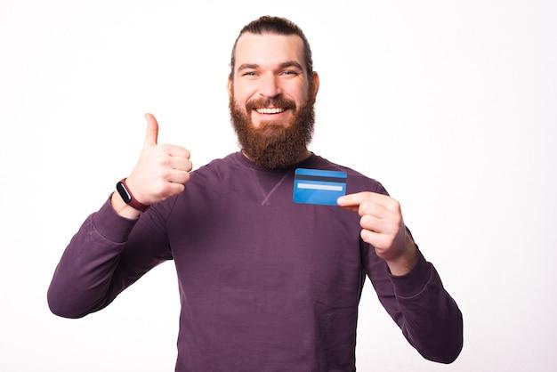 Bebaarde vrolijke man vertoont een duim en houdt een creditcard vast