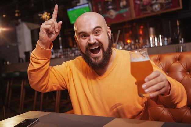 Bebaarde vrolijke man viert overwinning van zijn favoriete voetbalteam op sportbar