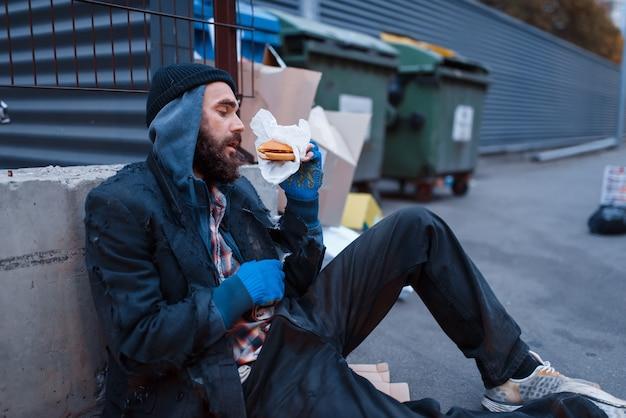 Bebaarde vuile bedelaar met voedsel dat bij de vuilnisbak op stadsstraat zit.