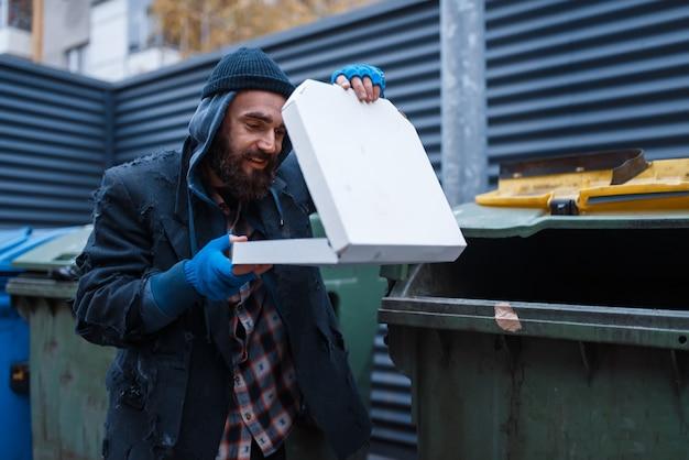 Bebaarde vuile bedelaar vond pizza in vuilnisbak op straat in de stad.