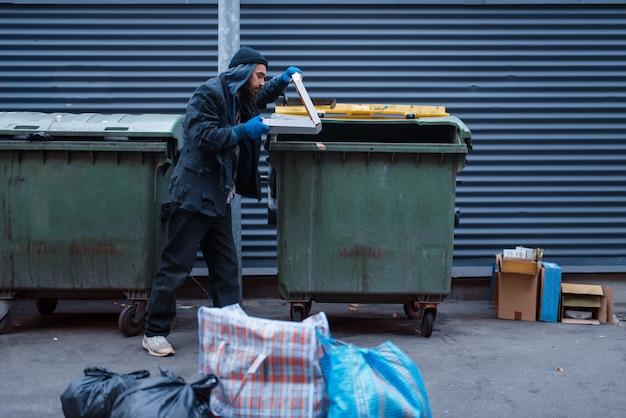 Bebaarde vuile bedelaar vond pizza in vuilnisbak