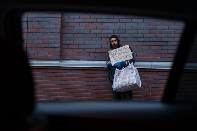 Bebaarde vuile daklozen bedelen op straat in de stad.