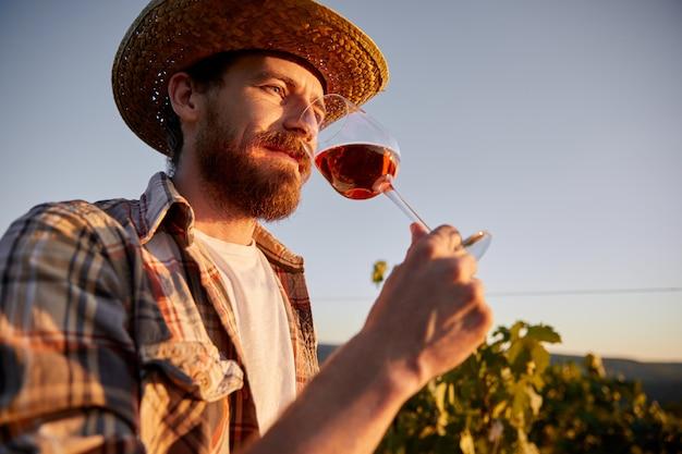 Bebaarde wijnmaker die van wijn op boerderij geniet