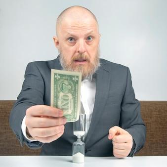 Bebaarde zakenman biedt betaling voor werk met geld tegen de achtergrond van de zandloper.
