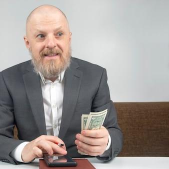 Bebaarde zakenman biedt betaling voor werk met geld tegen van de zandloper.
