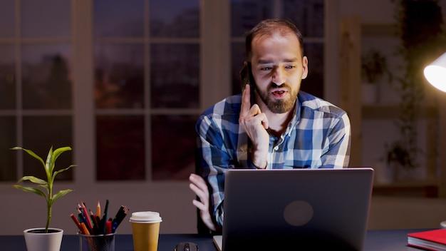 Bebaarde zakenman die een gesprek voert op zijn telefoon terwijl hij 's nachts in zijn thuiskantoor werkt.