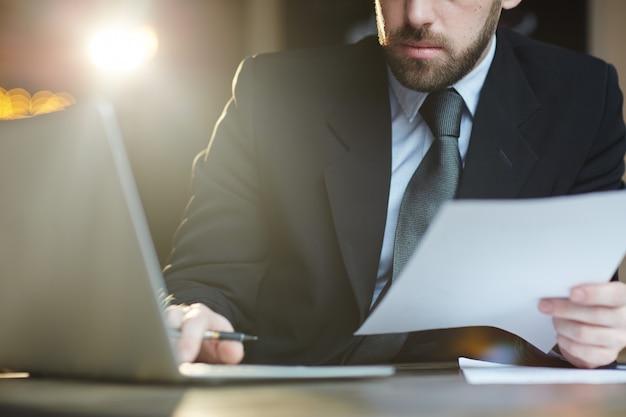 Bebaarde zakenman die met documenten in bureau werkt