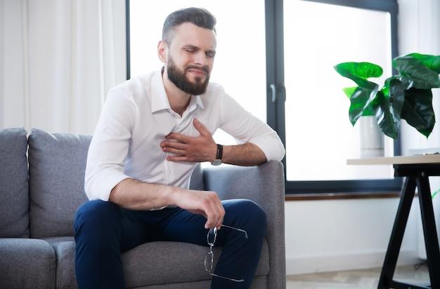 Bebaarde zakenman heeft een hartaanval als gevolg van stress en hard werken