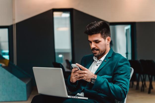 Bebaarde zakenman in bureau die smartphone gebruiken om bericht te verzenden.