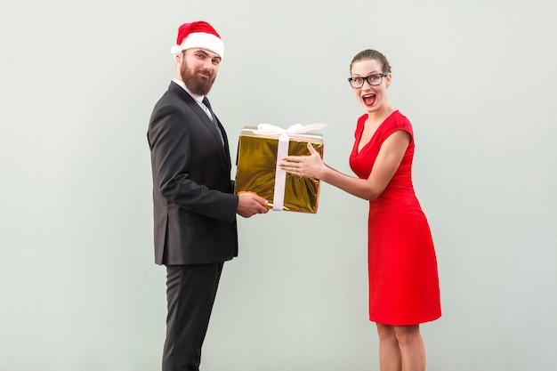 Bebaarde zakenman in kerstmuts geeft een cadeau mooie vrouw in rode jurk met verbaasd gezicht. studio opname op grijze achtergrond