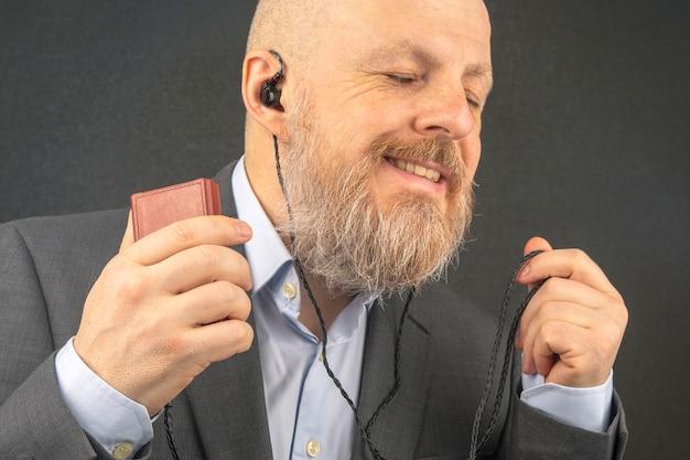 Bebaarde zakenman luistert graag naar zijn favoriete muziek van een audiospeler met een kleine koptelefoon. audiofiel en muziekliefhebber. muziek en hifi-geluid